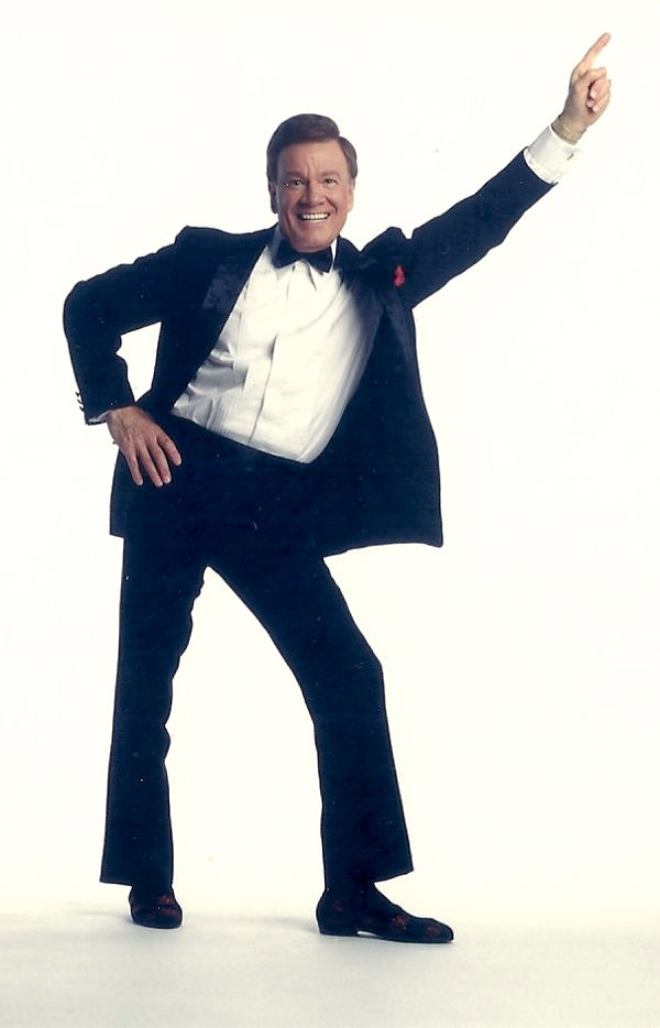 Wink Martindale in Tuxedo Doing Debt Pose